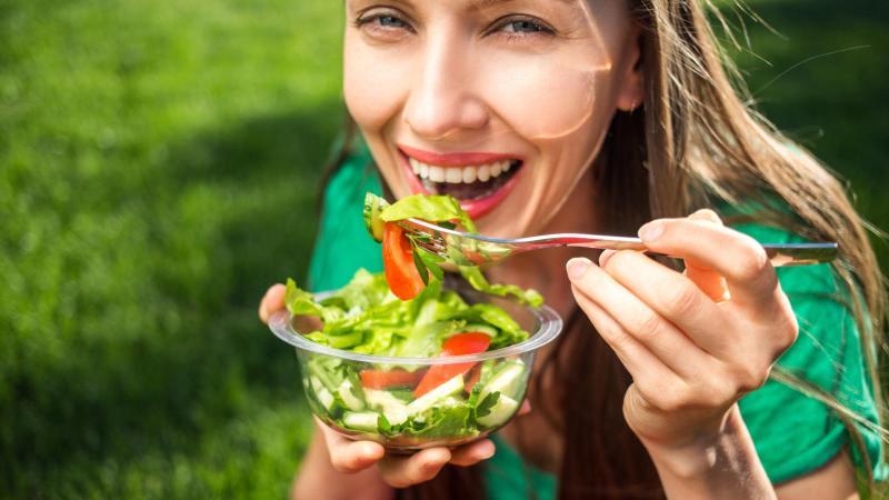 Usměvavá žena jí zeleninový salát.