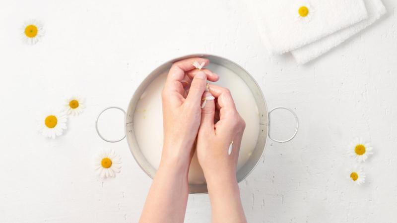 Žena si koupe ruce v heřmánkové vodě